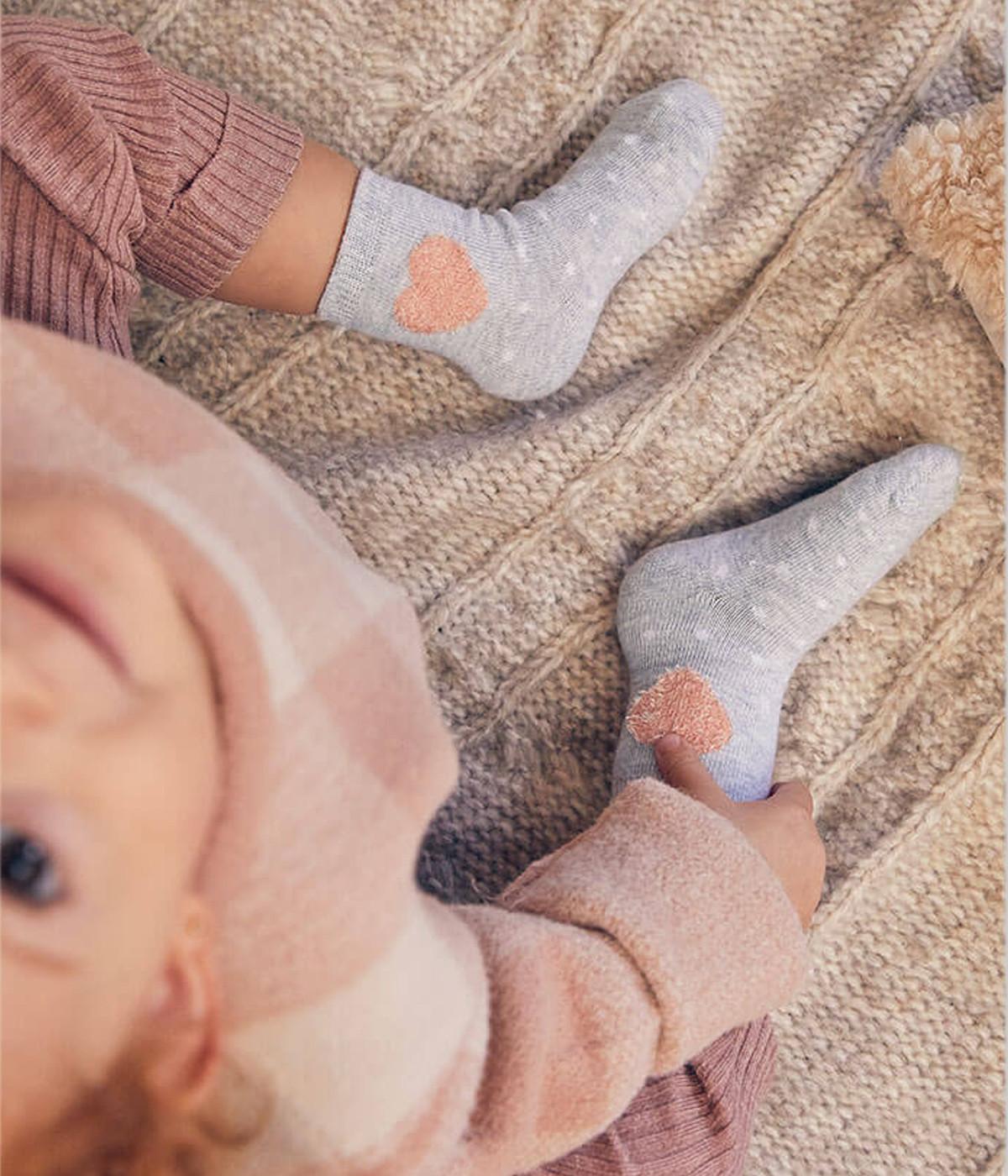 2 pares de meias cinza para bebé menina e recém-nascida. Par de meias com renda e laço cinza e outro par com coração rosa com relevo e pintinhas brancas por toda a parte do pé.